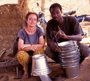 Tin-smiiths ||| Janet with the pails she made with Drissa's instruction. It took Janet a week to make 8 pails.