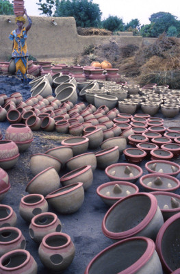 Pots Ready for Firing ||| Firings take place every Saturday and Sunday. By mid-afternoon, the unfired pots are brought to the firing place. This takes many hours. For each trip to the firing place, a woman carries at least two on her head and one in her hand. Visible here are pots for storing water, cooking, carrying embers, and wavy lipped flower pots.